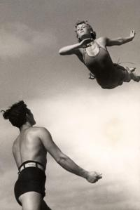 English: Seaside life. Man standing ready to catch a woman coming down with a swallow dive. Photograph from the Dutch illustrated magazine 'Het Leven' (bathing issue), 1937.